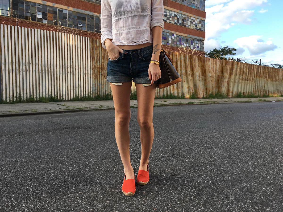Closeup of red Soludos with denim shorts and white top outfit