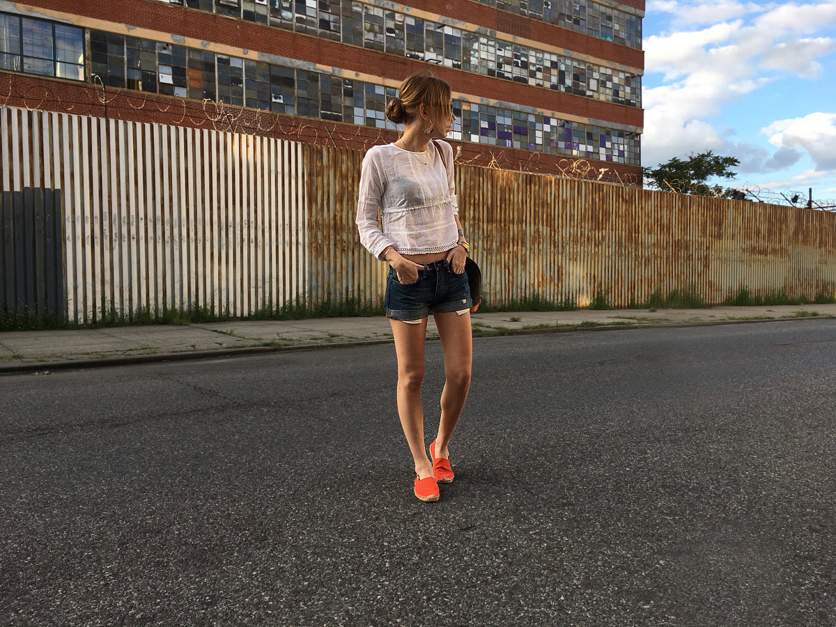 Red Soludos with denim shorts and white top outfit side view