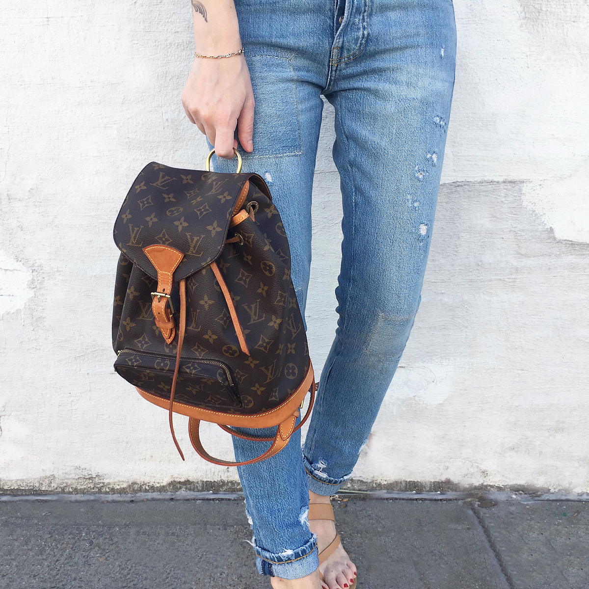 Louis Vuitton backpack and ripped jeans