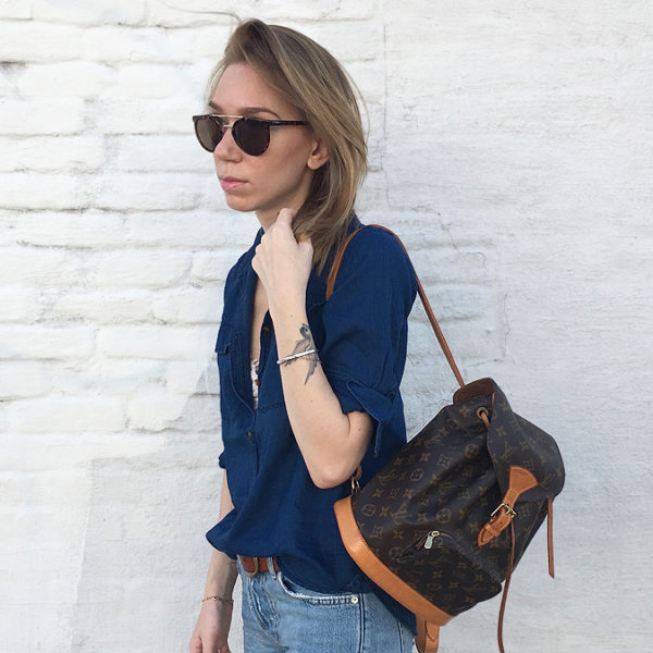 Girl wearing Louis Vuitton backpack against white wall