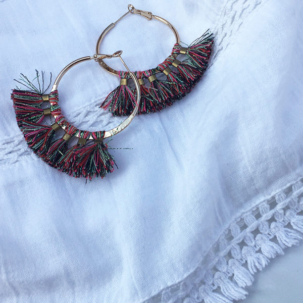 Gold hoops with colorful tassels and white shirt