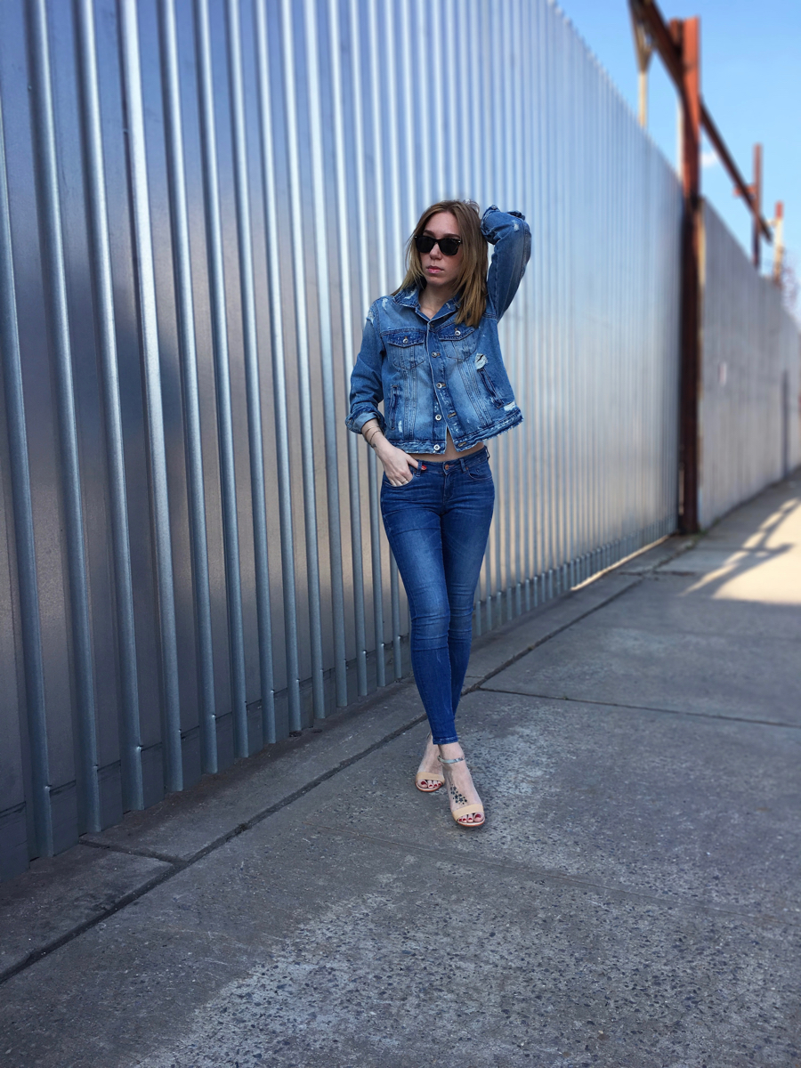Girl wearing denim jacket and denim jeans outfit posing with hand over head