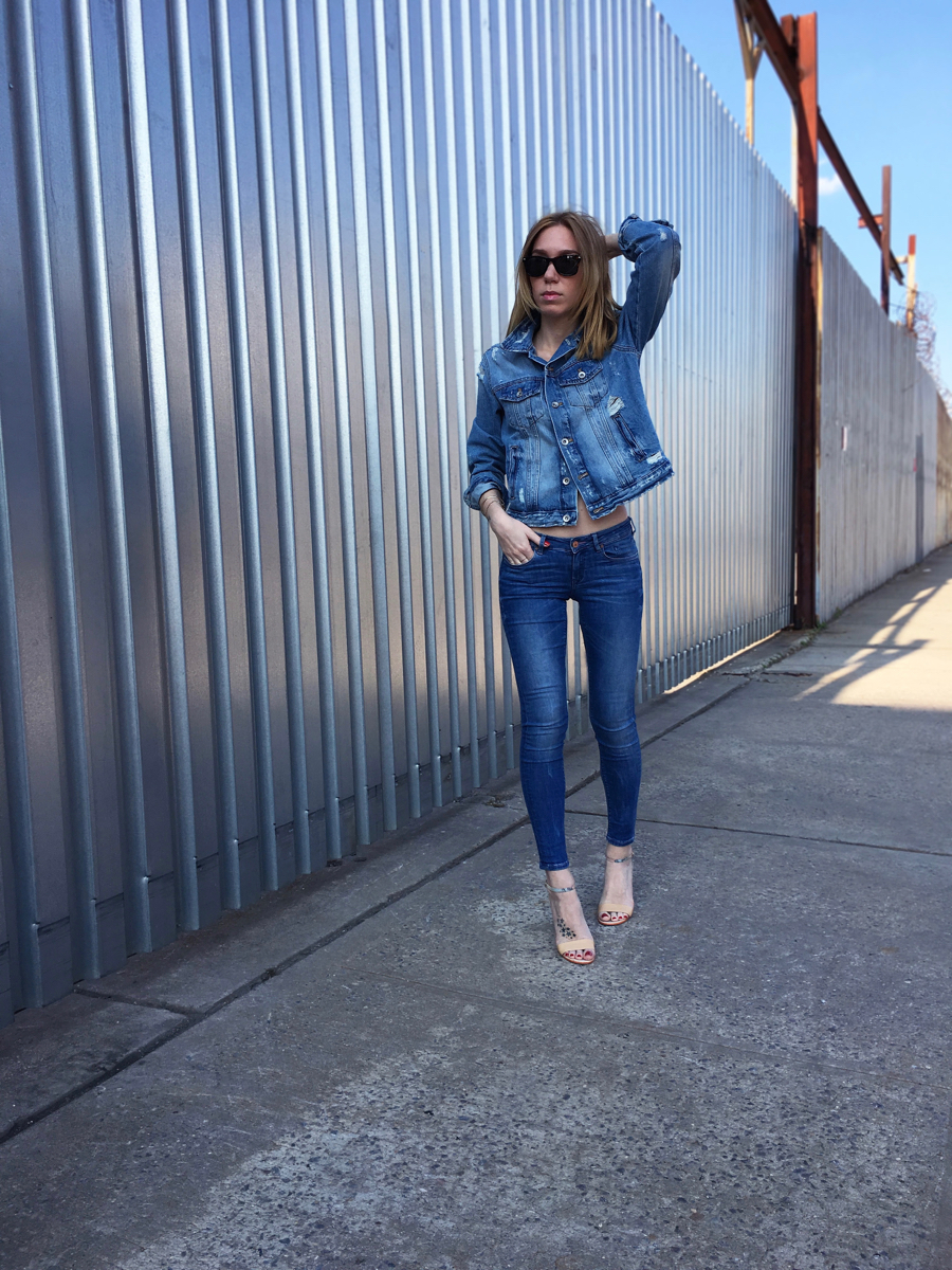 Girl wearing denim jacket and denim jeans outfit posing on the sidewalk