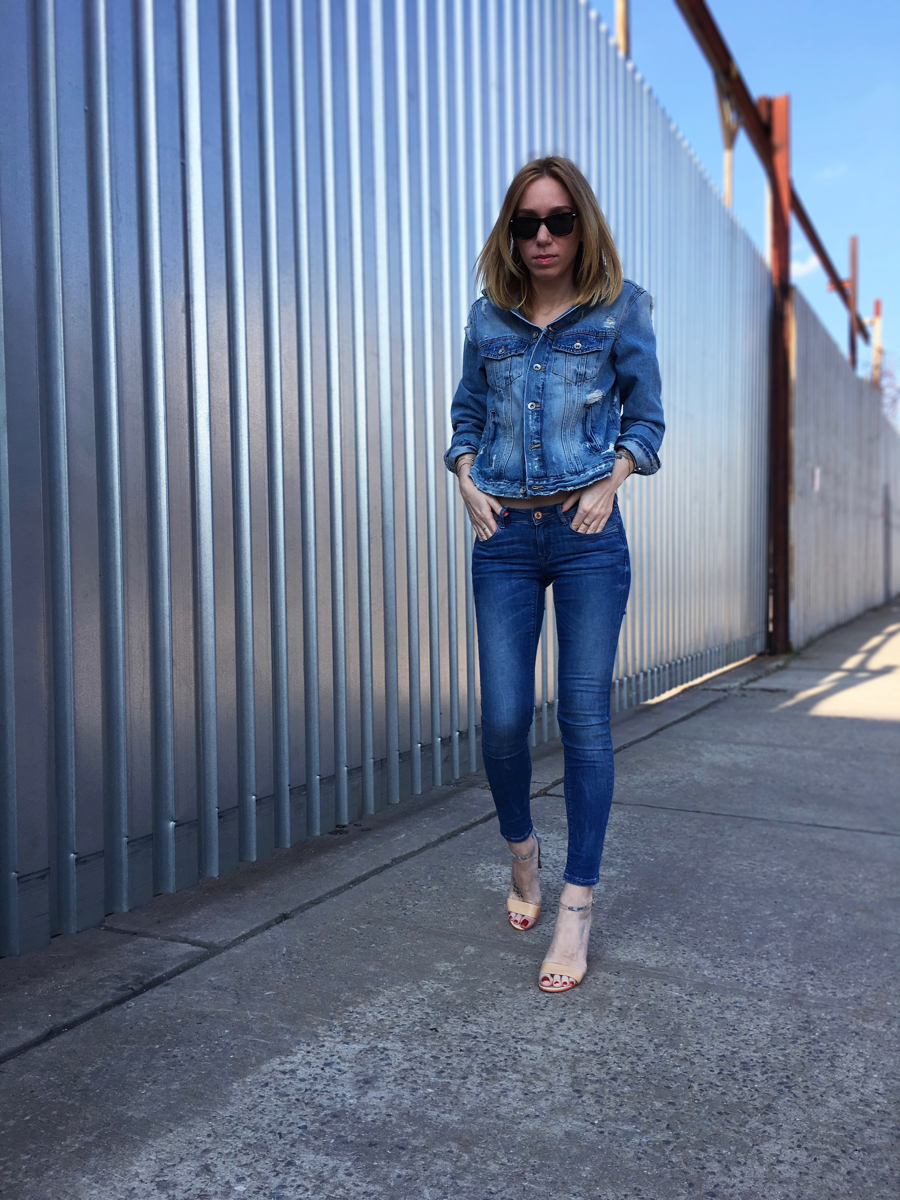 Girl posing in denim jacket and jeans on the sidewalk