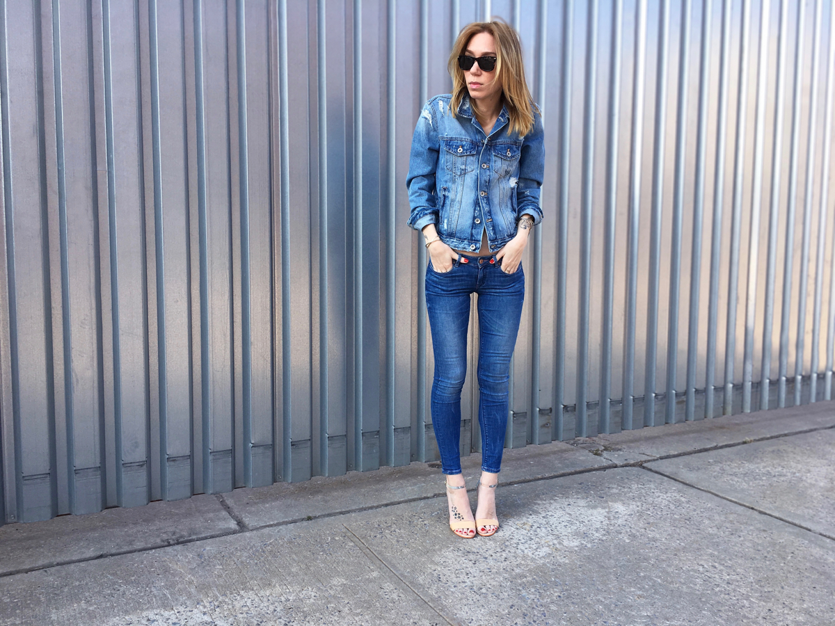 Girl wearing denim jeans and denim jacket outfit posing with hands in pocket