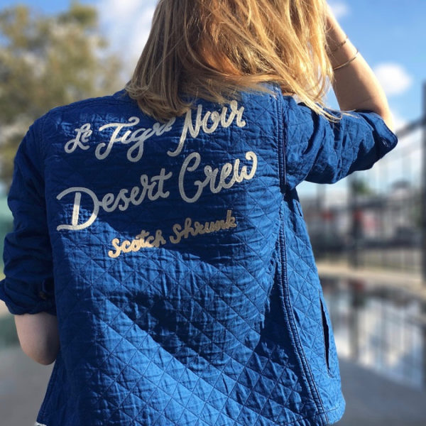 Woman posing back view wearing navy quilted shirt