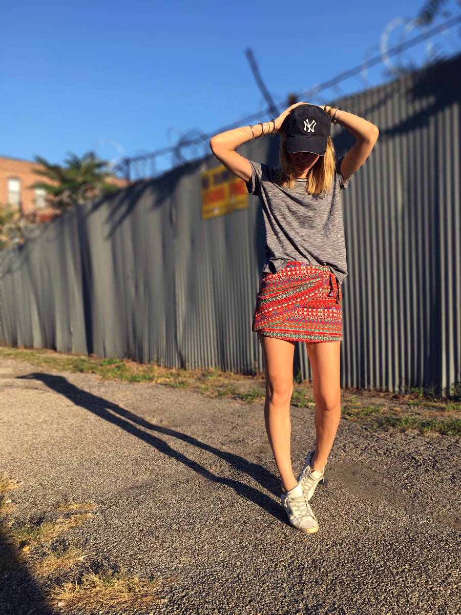woman wearing red mini skirt with grey tee and a Yankees cap posing on sidewalk