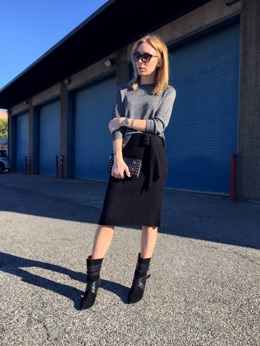 Woman posing wearing black pencil skirt with boots and grey sweater