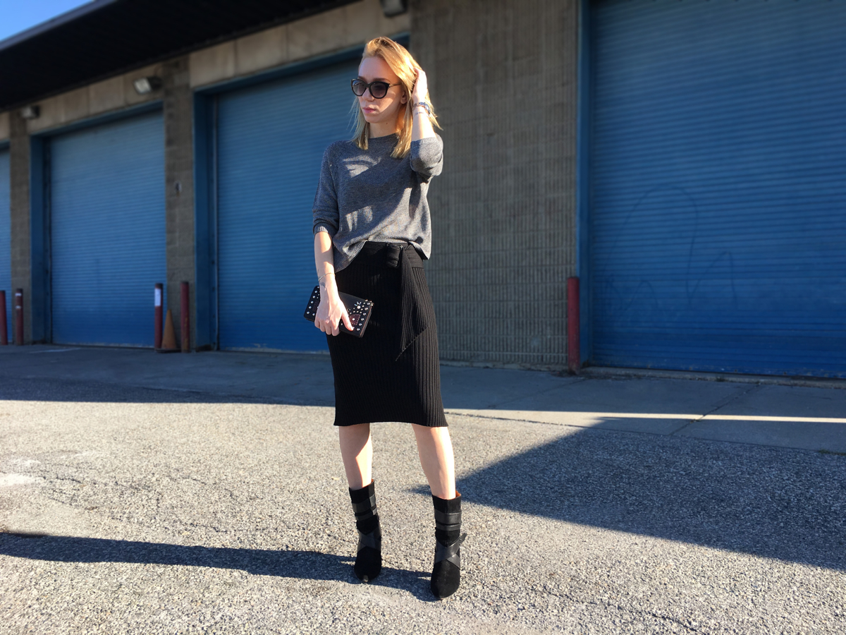 woman posing in black pencil skirt and grey sweater