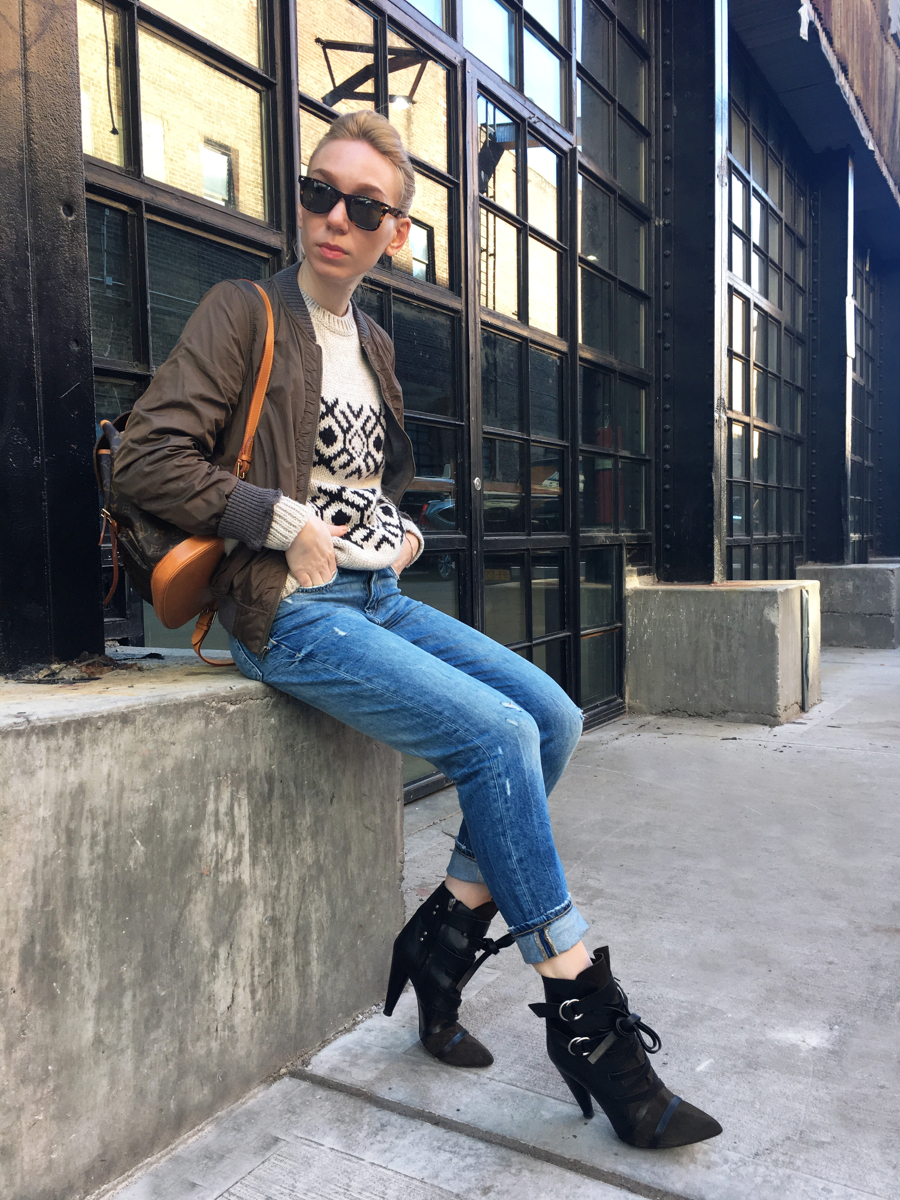 Woman sitting wearing jeans with green bomber jacket and heels
