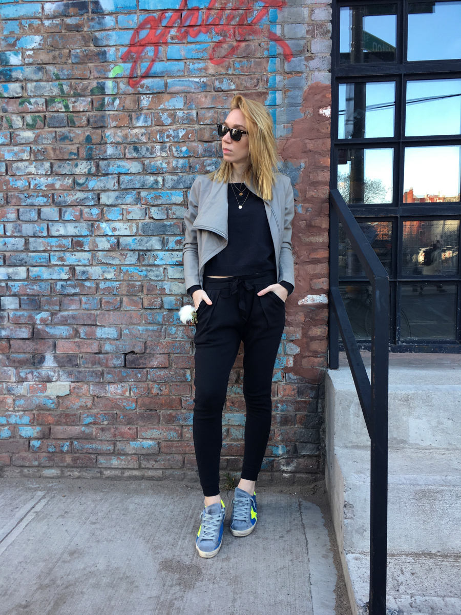 Woman posing against brick wall wearing sweats and Golden Goose sneakers