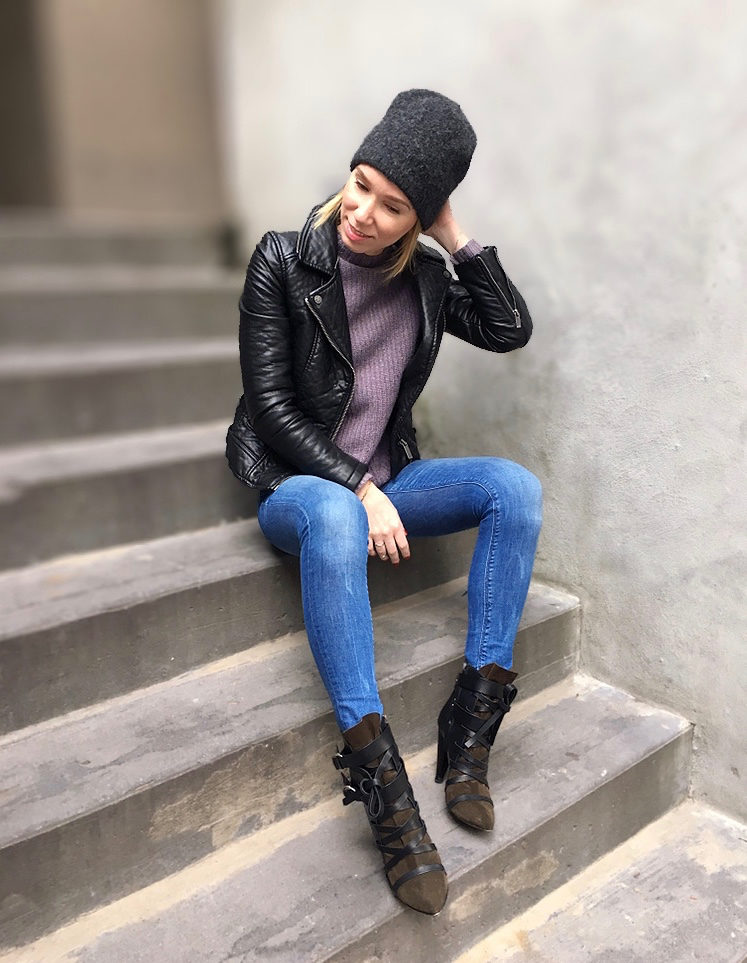 Woman sitting posing in leather jacket and jeans