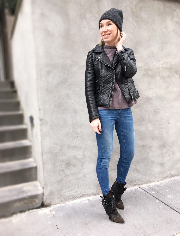 Woman posing in leather jacket and jeans outfit