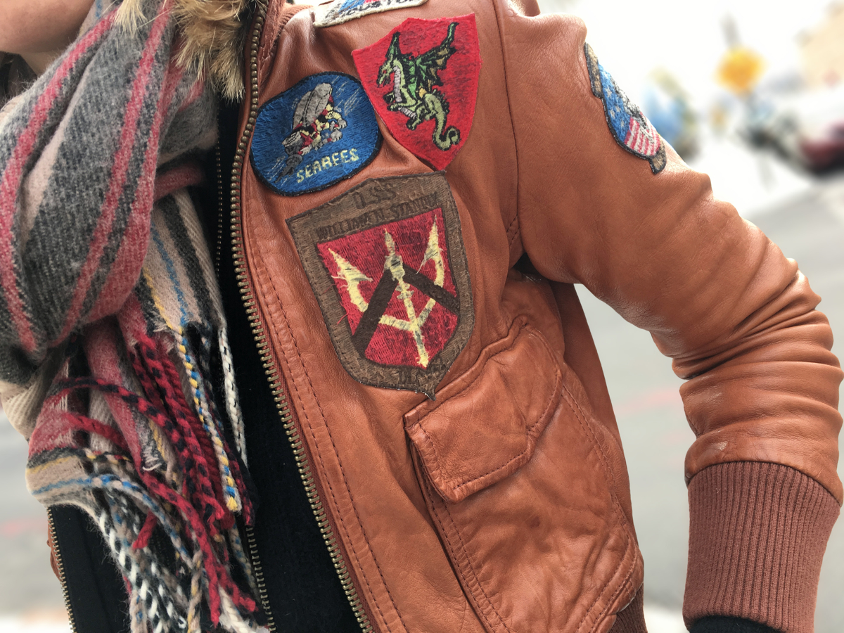 Detail shot of brown leather jacket with patches