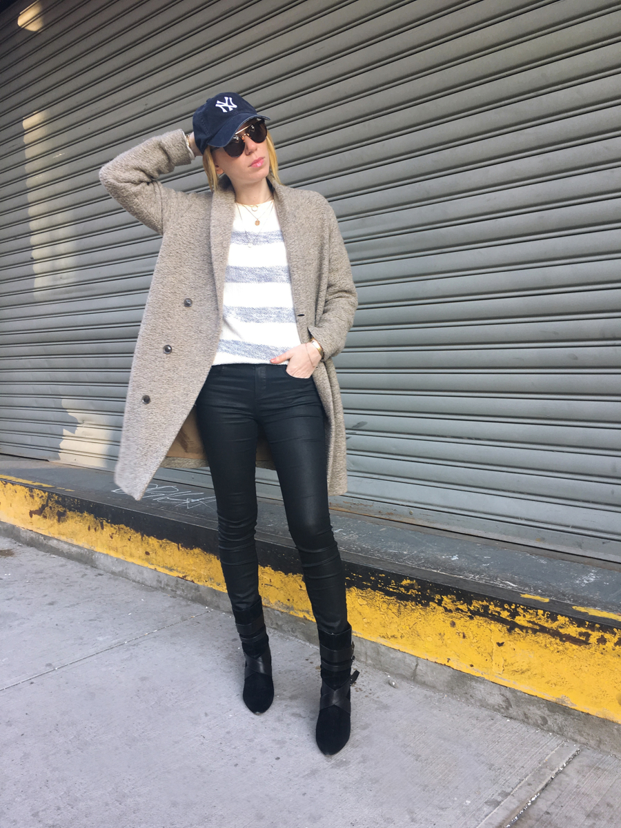 Woman posing with hand on head wearing beige coat and black jeans