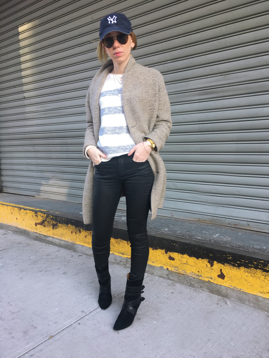 Woman posing with hands in pockets wearing beige coat and black jeans