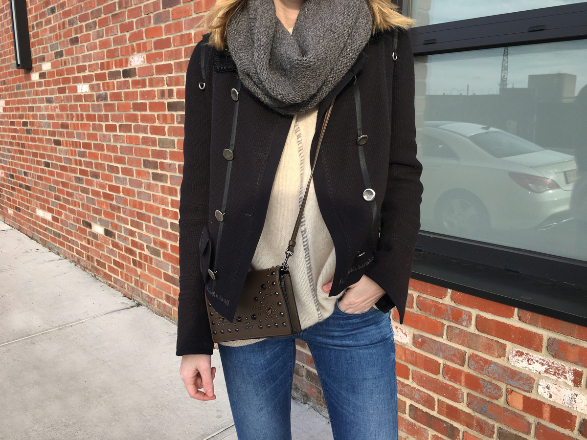 Detail shot of navy coat, beige sweater and grey scarf