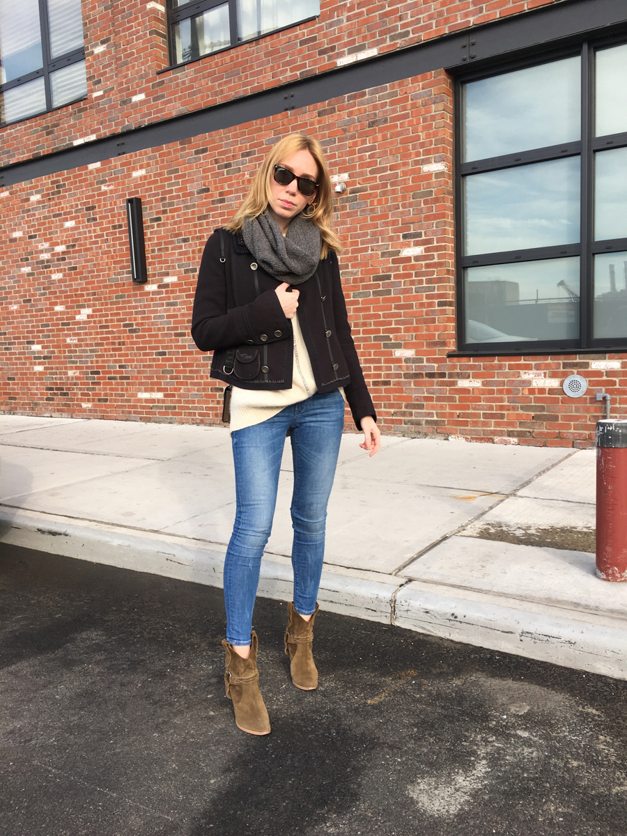 Woman standing in street wearing beige sweater and navy coat in jeans