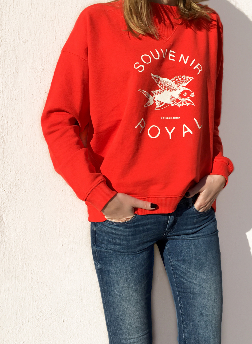 Red sweat shirt against white wall