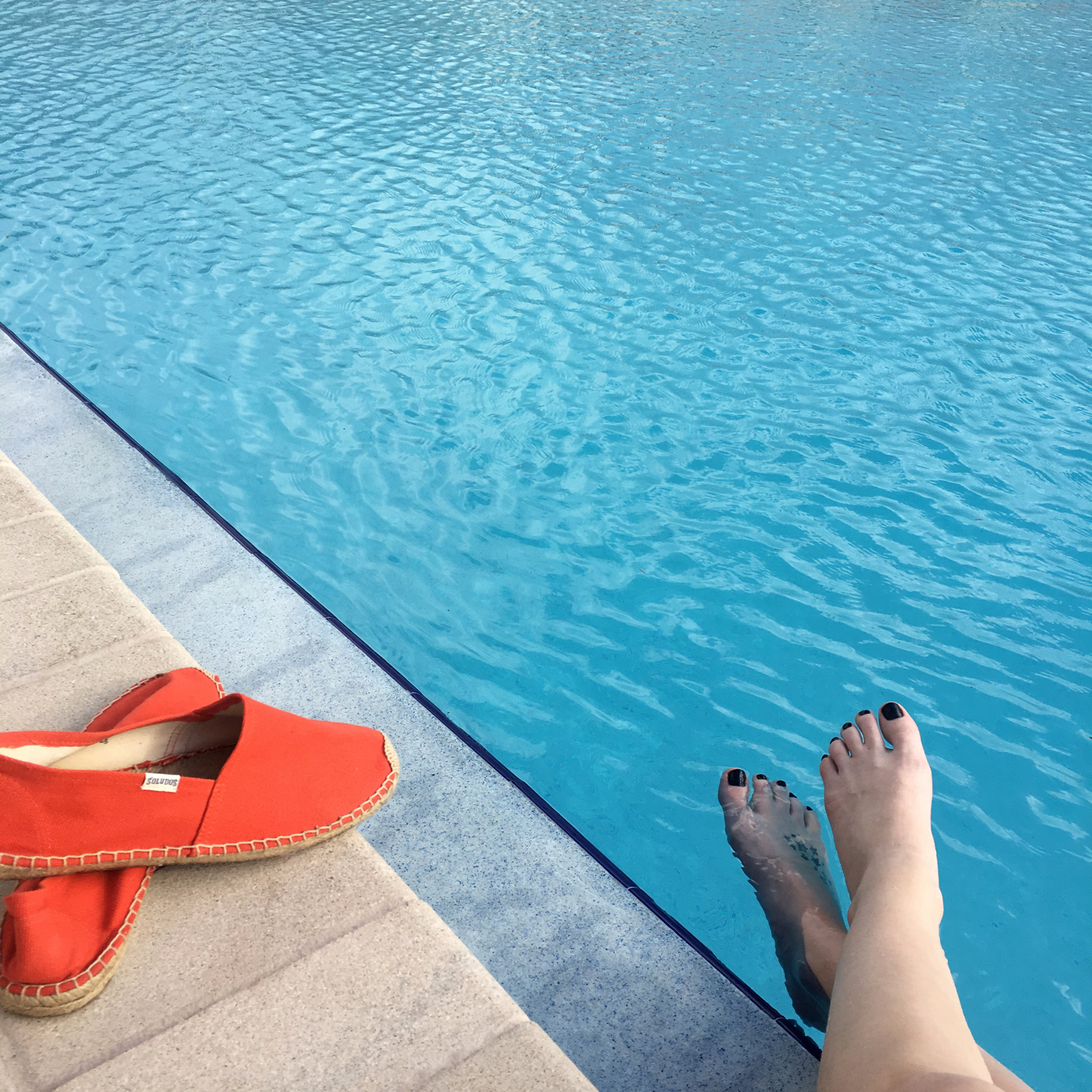 Feet by a poolside with red shoes near the edge