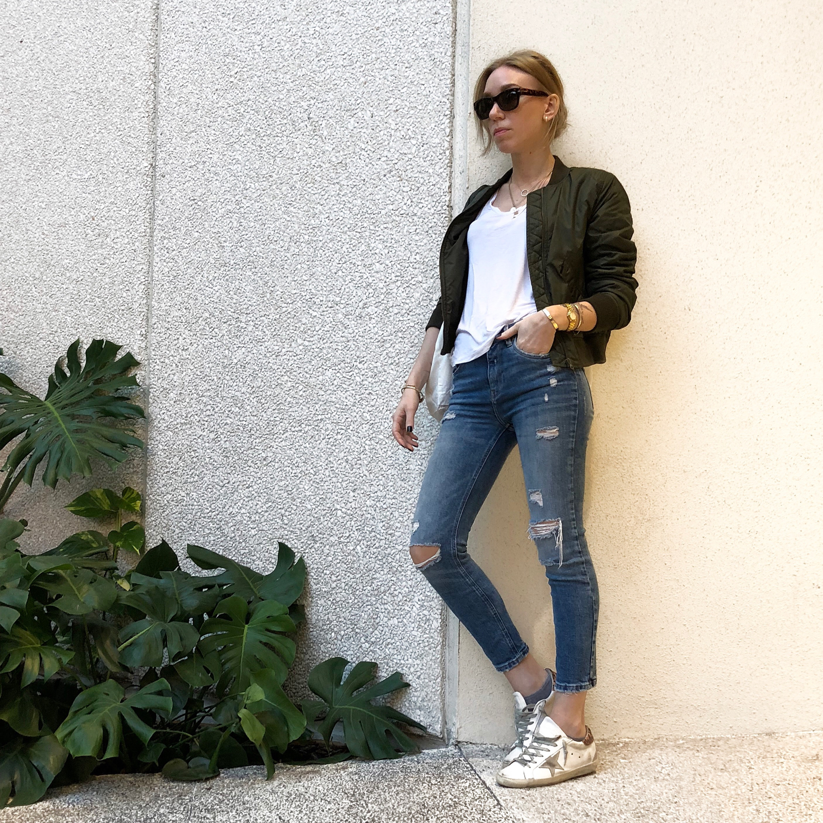 Woman posing in denim and olive jacket against white wall