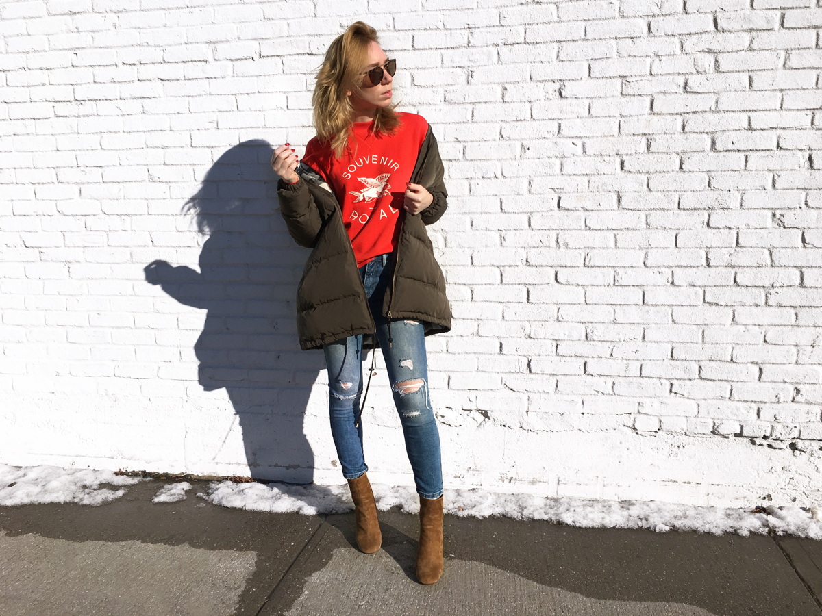 Woman posing against white brick wall wearing red sweater and olive jacket