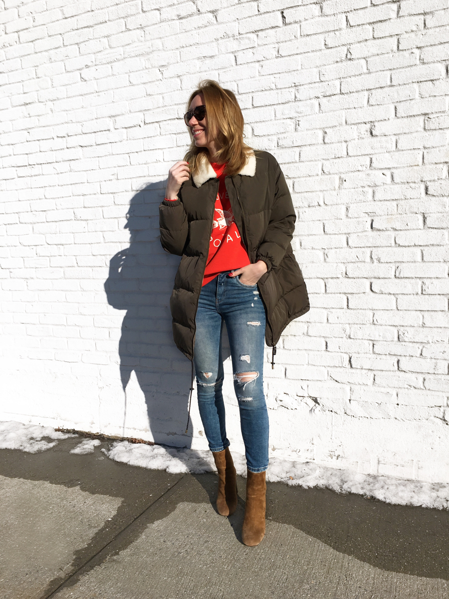 Woman posing in olive coat with jeans and booties
