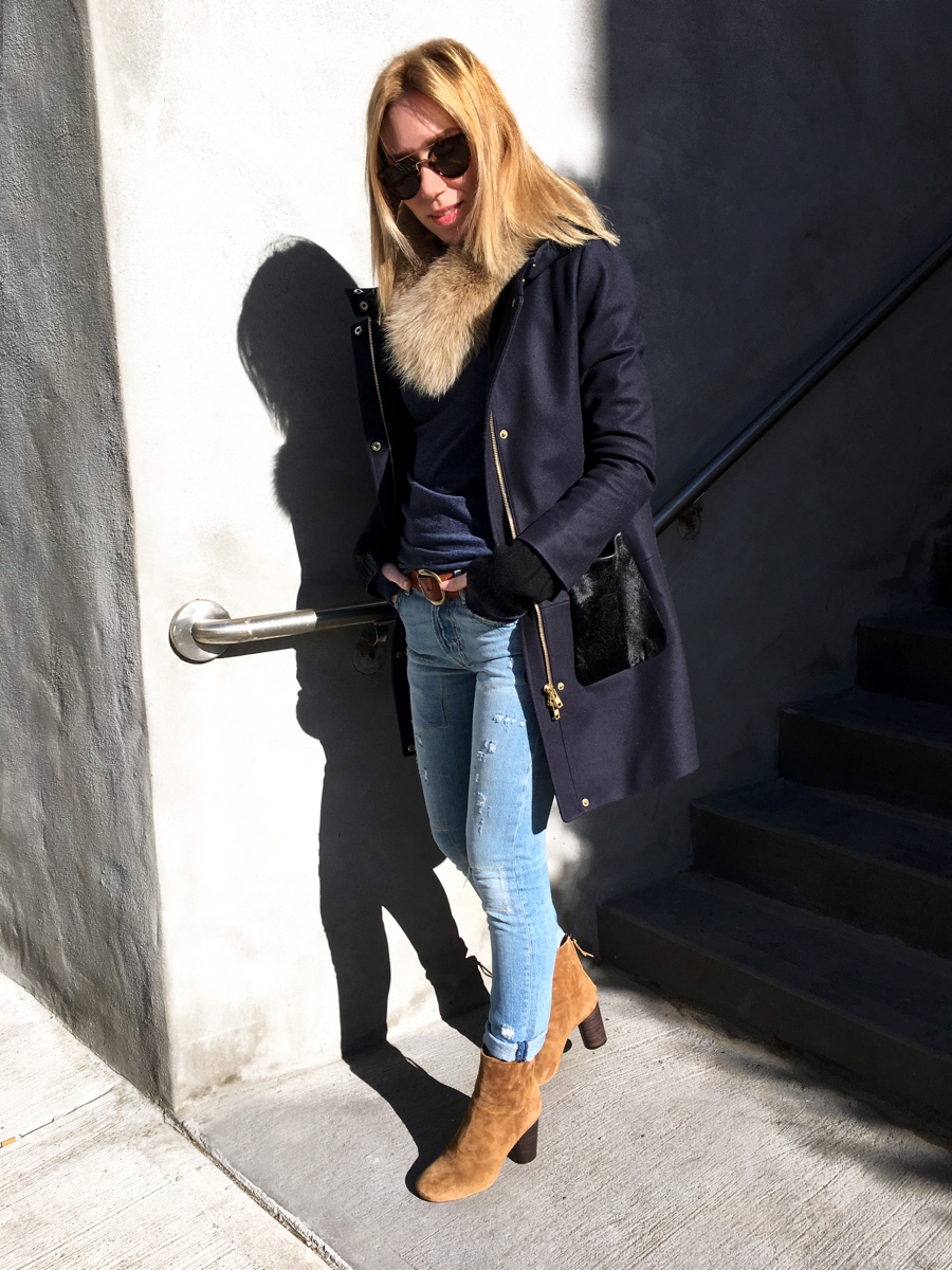 Woman posing in jeans and navy coat