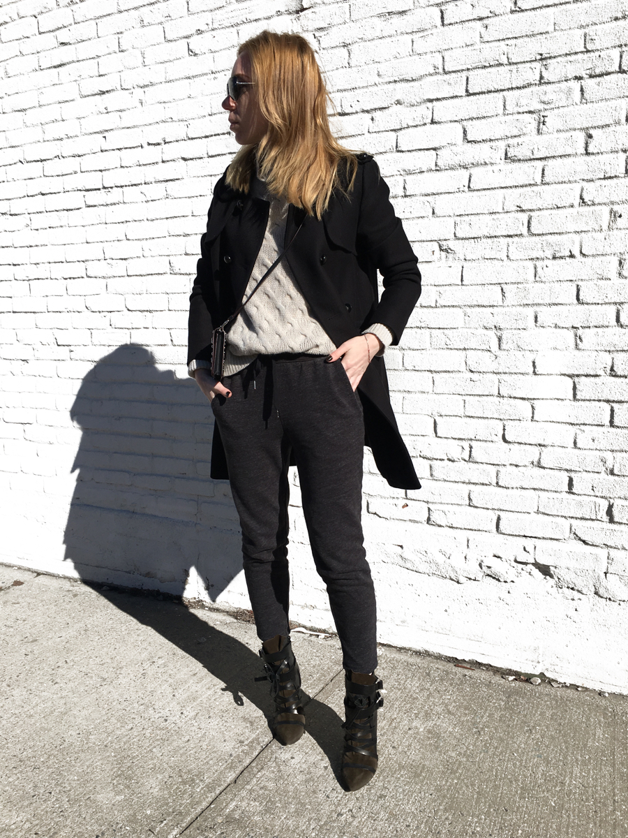 Woman posing in outfit against white brick wall wearing sweats and heels