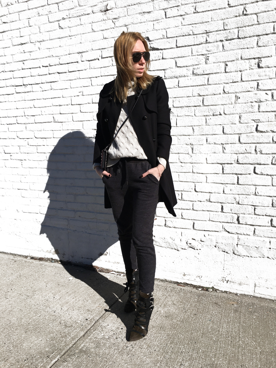 Woman posing wearing black coat with sweats and heels