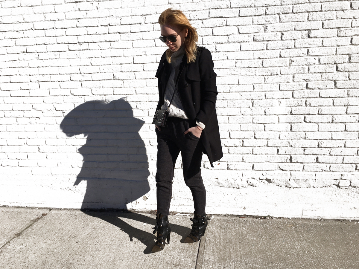 Woman posing against white wall wearing sweats and heels with black coat
