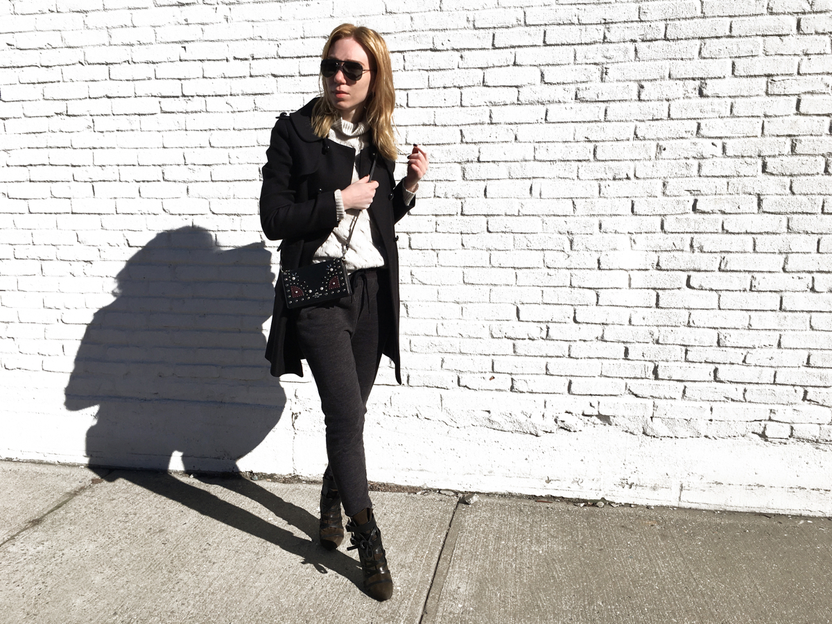 Woman posing in sweats and a coat against white wall